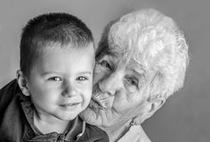 Old and young. A little boy with her great-grandmother - opposites attract- old and young Stock Image