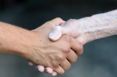 Old and young man shaking hands Royalty Free Stock Photo