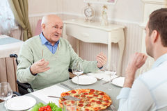 Old and young men have a dinner in restaurant Stock Images