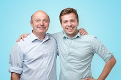 Old and young men standing together on blue studio wall. stock photos