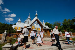 Old and young village people walking past the wooden Orthodox church stock image