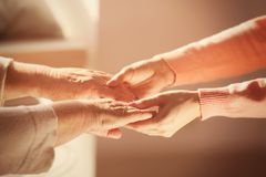 Old and young women holding hands on blurred background. Closeup Stock Photo