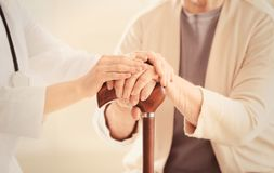 Old and young women holding hands on walking stick. Closeup stock photos