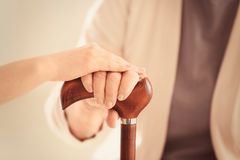 Old and young women holding hands on walking stick. Closeup royalty free stock images