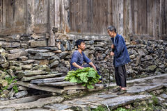 An old and younger farmers talking near wooden shed. Royalty Free Stock Photo