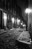 Oldboston. Old 19th Century cobble stone road in Boston Massachusetts, lit only by the gas lamps revealing the shuttered windows and brightly lit doorways of the royalty free stock images