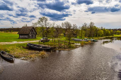 Olde小屋和小船在河沿 免版税库存照片