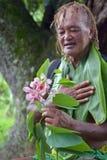 Olde åldrades manblickar för Stillahavs- öbo på den exotiska blomman på ecotou arkivbilder