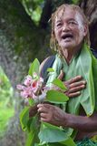 Olde aged Pacific Islander man explains about exotic flower on e. Olde aged Pacific Islander man age 75 explains about exotic flower on eco tourism tour in stock photos