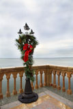 Olde Tyme Lamp Post decorated for Christmas. Olde Tyme light post decorated with a red Christmas bow, trimmed in gold, hanging from a pine wreath.The lamp post royalty free stock photography