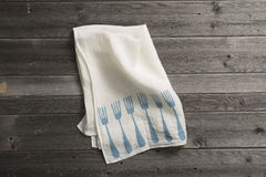 Olded Napkin with Blue Fork Pattern on Wooden Surface Royalty Free Stock Photo