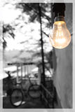 Olden Day Memory. Lighting bulb beside wooden house in a village yellow yellowish golden collour monochrome grayscale background Stock Photo