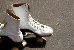 Olden Roller Skates. A pair of well used, adjacent roller skates awaits the next skater to exercise Stock Photo