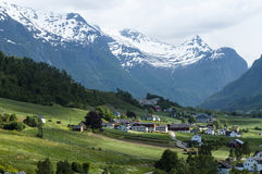 Olden village. Sunlight on Olden village with snow capped mountains in background Royalty Free Stock Photography