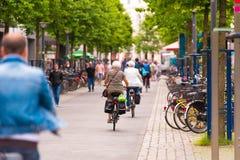 OLDENBURG TYSKLAND - JUNI 10, 2017: En grupp av cyklister som rider runt om den gamla staden Kopiera utrymme för text Arkivfoto