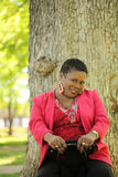 Older African American woman outdoors. Older black woman outdoors portrait tree trunk in background Stock Photography