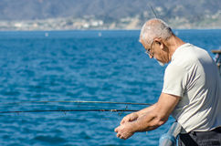Older aged man fishing off a pier, Santa Monica Royalty Free Stock Images