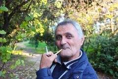 Older Armenian Man smoking a pipe in the park Athens Greece 1-3-2018. An older Armenian Man smoking a pipe in the park Athens Greece 1-3-2018 Stock Photos
