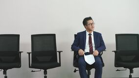 Older asian corporate executive waiting in chair for job interview