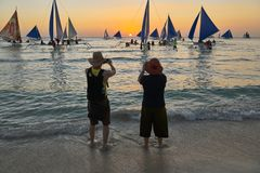 Older Asian couple enjoying taking pictures at sunset on Boracay royalty free stock photography