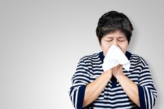 Older asian woman is having flu and sneezing from sickness seasonal virus problem. With background. Fever and cold in senior people with influenza illness and stock photos