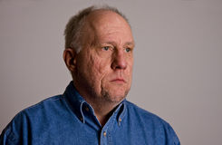 Older Bald Guy in Blue Denim Shirt Serious to Left stock images