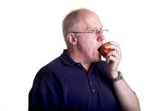 Older Bald Guy in Glasses Eating a Peach Stock Photos