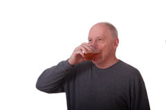 Older Balding Man in Gray Shirt Drinking Iced Tea Royalty Free Stock Images