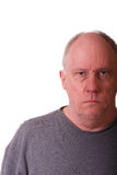 Older Balding Man with grumpy expression. An older balding man in gray shirt looking grumpy or mad stock image