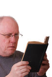 Older Balding Man Reading a Black Book or bible Royalty Free Stock Photos