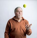 Older bearded man in orange sweater tossing green tennis ball Royalty Free Stock Images