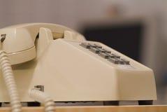 Older biege phone 06. Side angle close up of older biege phone a desk Stock Photos