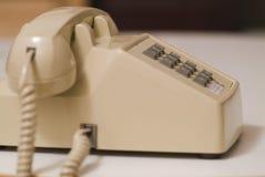 Older biege phone 07. Side angle older biege phone a desk Stock Image