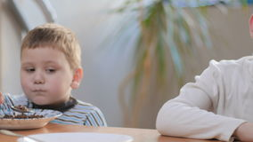The older boy do not want to eat flakes with milk at home stock video footage