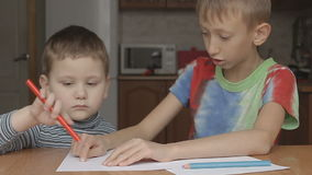 The older boy helps to draw a crayon stock footage