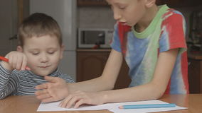 The older boy shows how to draw a crayon stock footage