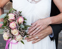 Older bride and groom hands and rings with flowers Stock Photos