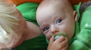 Older brother gives his younger one pacifier Stock Photos