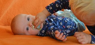 Older brother gives his younger one pacifier Royalty Free Stock Photography