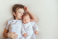 Older brother hugging his newborn sister. Children in bright clothes on a white blanket. Stock Image