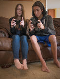 Older Brother Teaching Younger sister how to work a video game controller. Two teens sitting on a living room couch.  The older boy / brother is teaching the Royalty Free Stock Photos