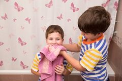 Older brother wipe his younger brother in the bathroom. Older brother wipe his younger brother with pink towel in the bathroom Stock Images