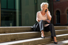 Older business woman is calling on stairs Stock Photos