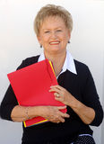 Older business woman with file folders. A senior business woman holding file folders Stock Image