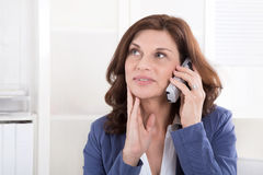 Older business woman making a phone call. Satisfied older woman listening or dreaming on telephone Royalty Free Stock Images