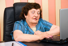 Older business woman in office using laptop Stock Photos