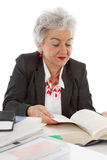 Older business woman sitting at desk reading in a book. Concept Stock Photos