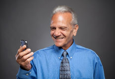 Older Businessman laughs at text message Royalty Free Stock Photography