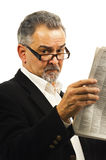Older businessman reads his newspaper. Royalty Free Stock Image