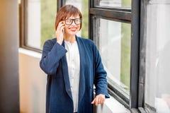 Older businesswoman talking phone indoors Stock Image